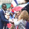 Les joueurs de l'équipe de France de football signent des autographes aux supporters à la sortie de l'Elysée à Paris le 11 juillet 2016