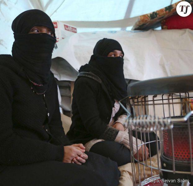 Deux femmes Yézidi, chassées de leur maison par l'Etat islamique, se réchauffent dans leur tente le 10 janvier 2015.
