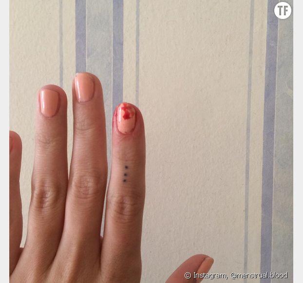 Une goutte de sang sur un doigt tatoué.