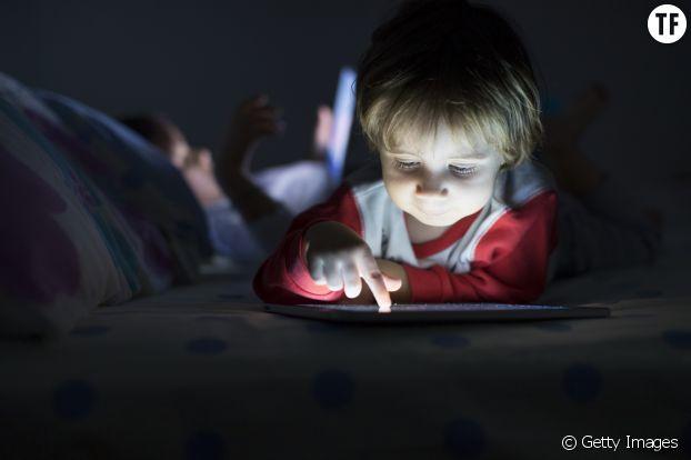 Un enfant face à un écran avant le coucher.