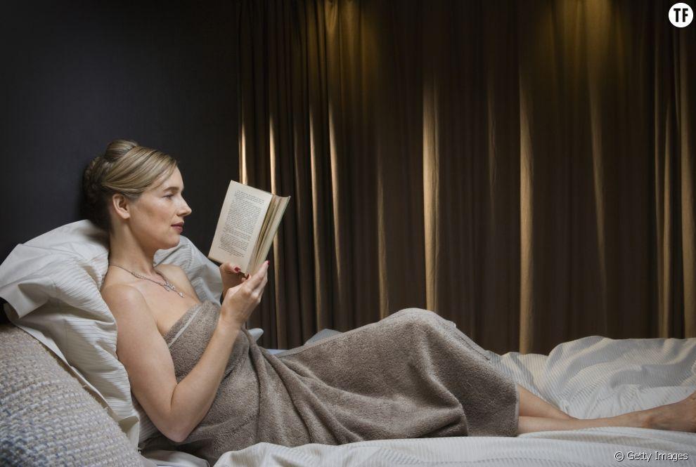 Une femme se détend en lisant un livre avant le coucher.