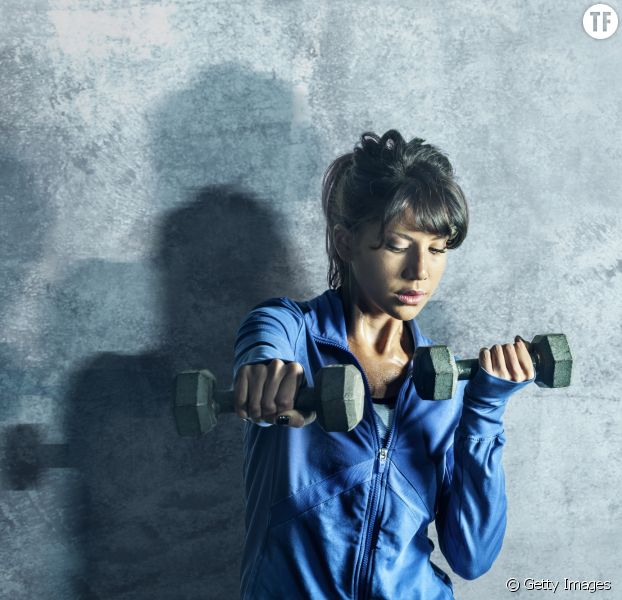 Un femme tient des poids après une séance de sport.