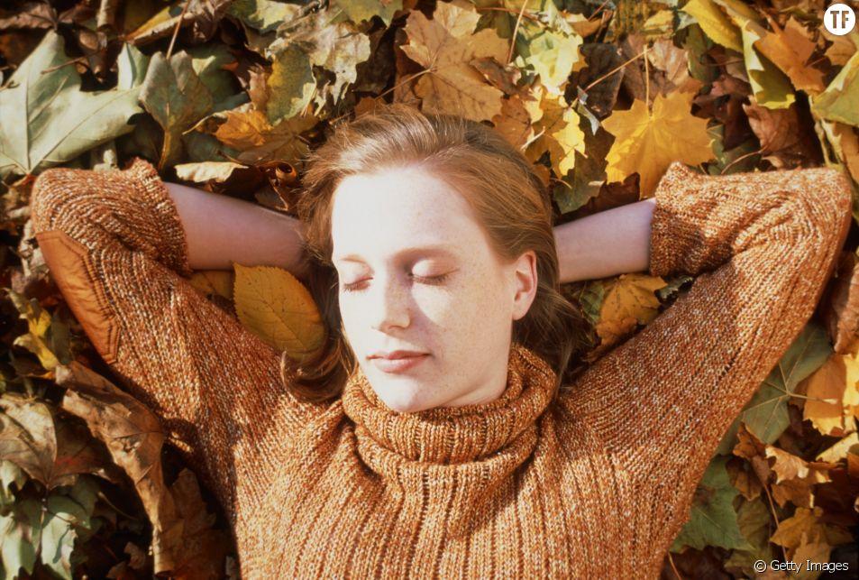 Une femme dort allongée sur le sol recouvert de feuilles mortes.