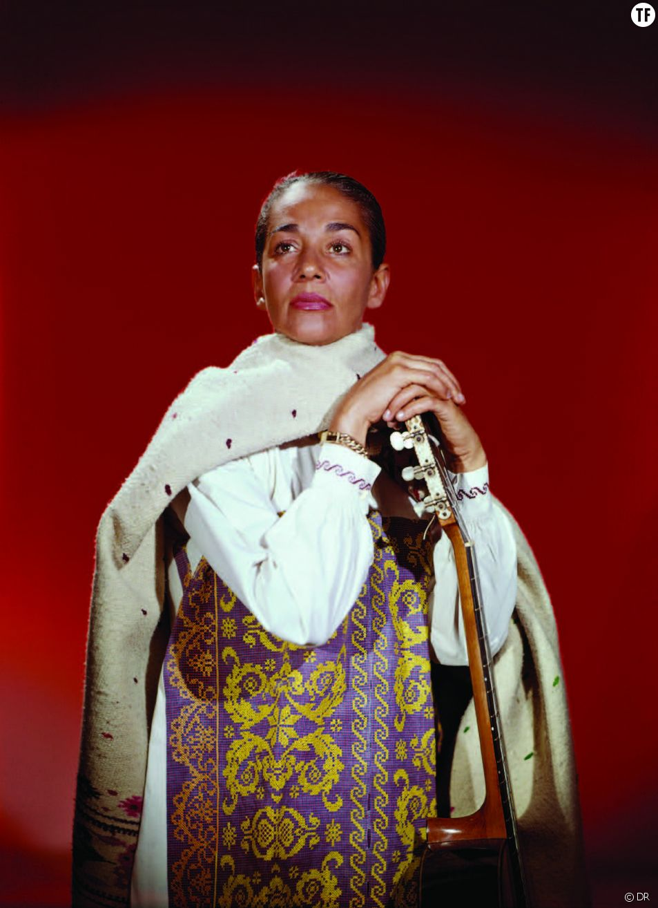 Chavela Vargas enveloppée dans son légendaire poncho, avec sa guitare.