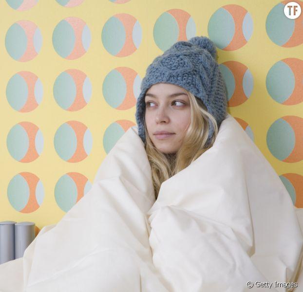 Photo d'illustration d'une femme ayant froid dans sa chambre.