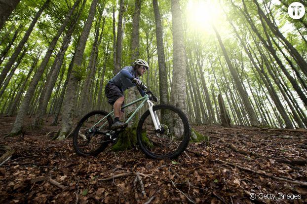 Photo d'un homme en train de faire du vélo en forêt.
