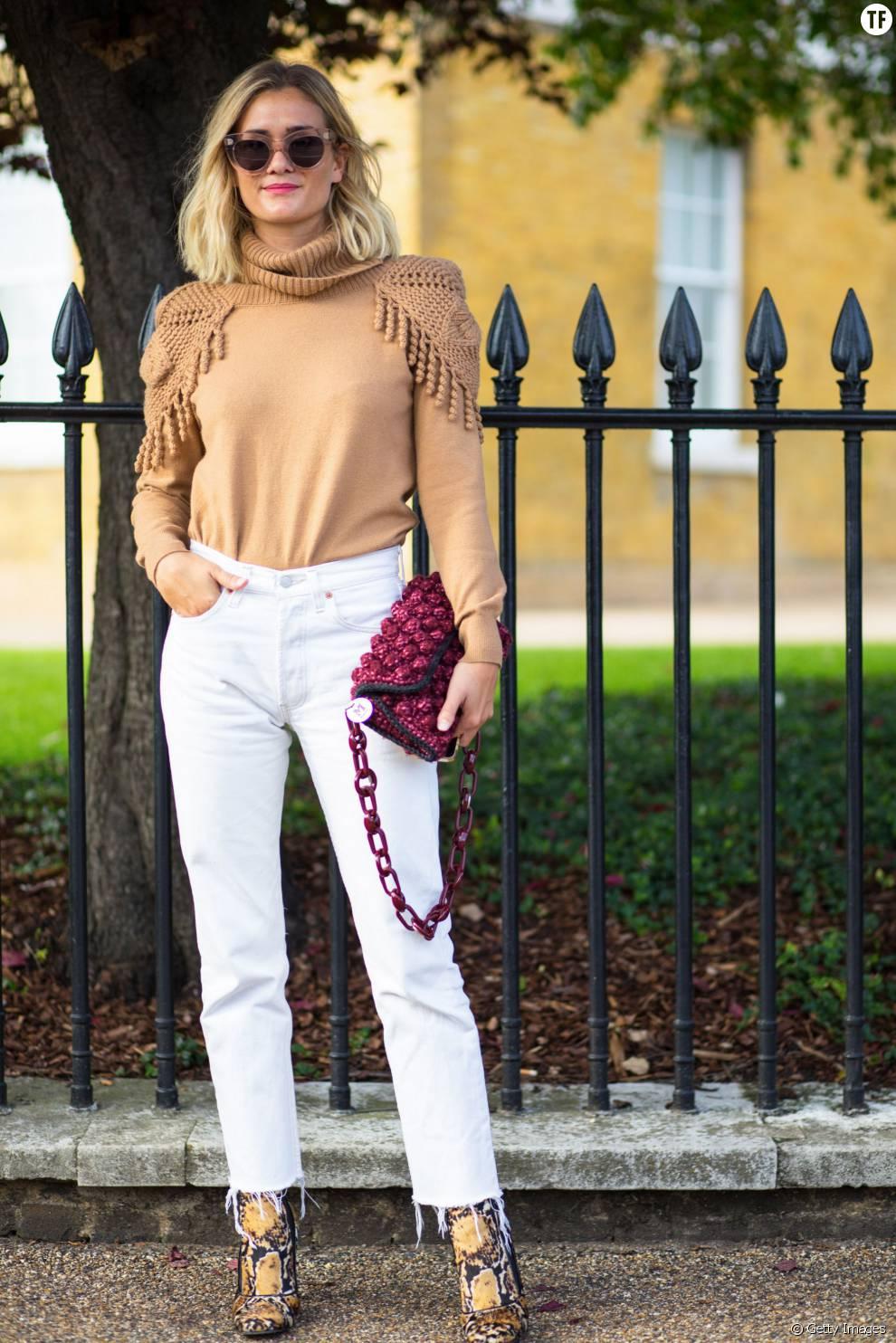 Une tenue 100% féminine en jean blanc et pull à épaulettes