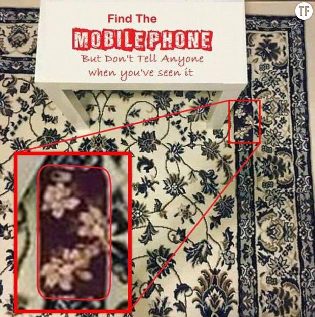 On peut repérer le téléphone grâce à la différence de motif dans la tapisserie