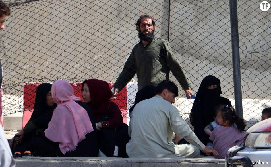 Un membre des talibans monte la garde alors que les Afghans se rassemblent devant l'aéroport de Kaboul en Afghanistan, le 24 août 2021.