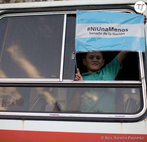 """Un jeune garçon tient le drapeau argentin avec l'inscription """"Pas une de moins"""" lors des manifestations à Buenos Aires."""