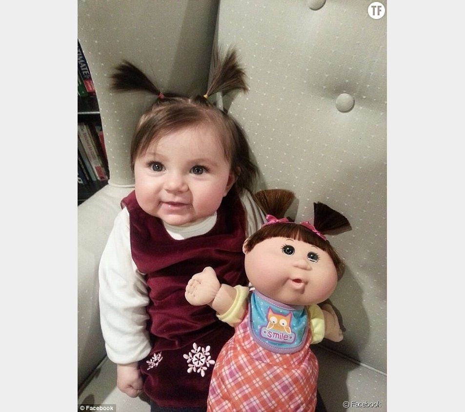 Cette petite fille à couettes n'est-elle pas à croquer avec sa poupée ?