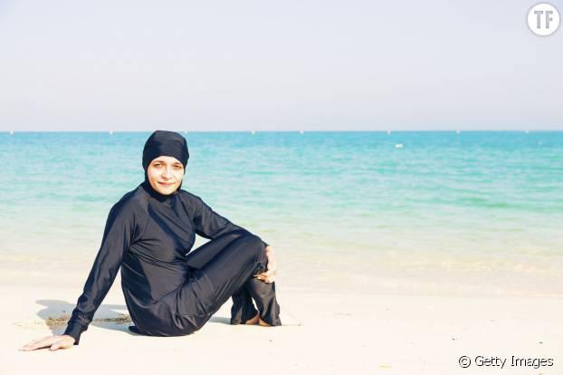 Une femme en burkini au bord de la plage