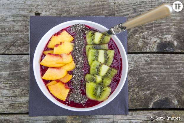 Smoothie bowl sur lit de fruits rouges avec morceaux de kiwi, de pêche et graines de chia