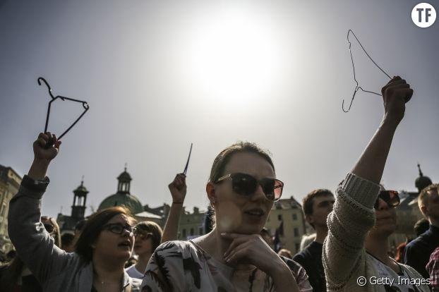 Ds femmes qui manifestent pour l'avortement brandissent un cintre, triste symbole des meurtriers avortements clandestins