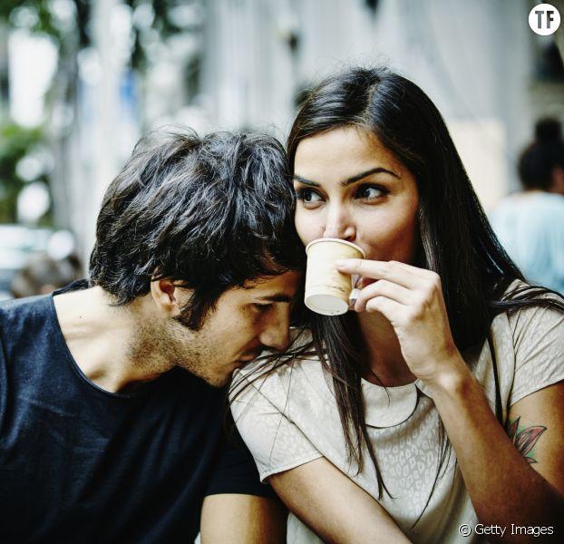 Elle boit un café songeuse, à côté d'un homme.