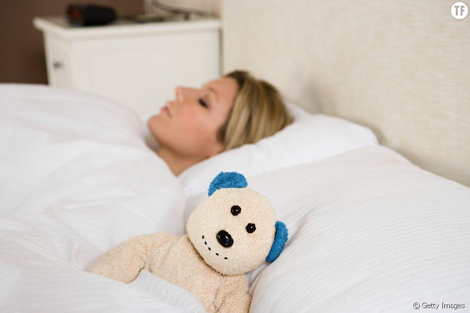 Une femme dort seule à côté d'un ours en peluche.