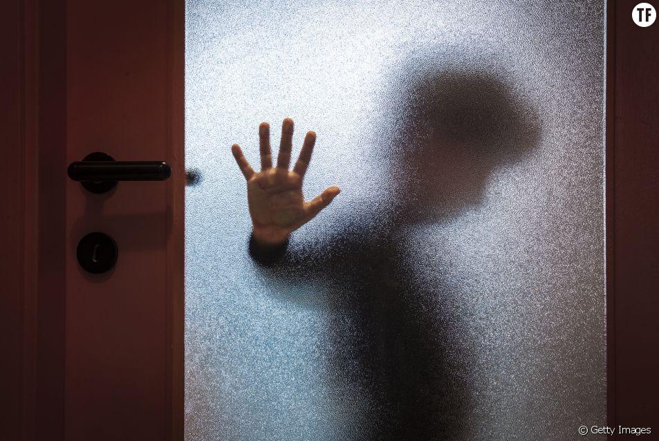Photo d'illustration d'une femme derrière une porte.