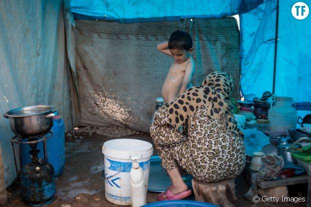 Une Syrienne lave son fils sous une tente après la libération de Raqqa, en Syrie.