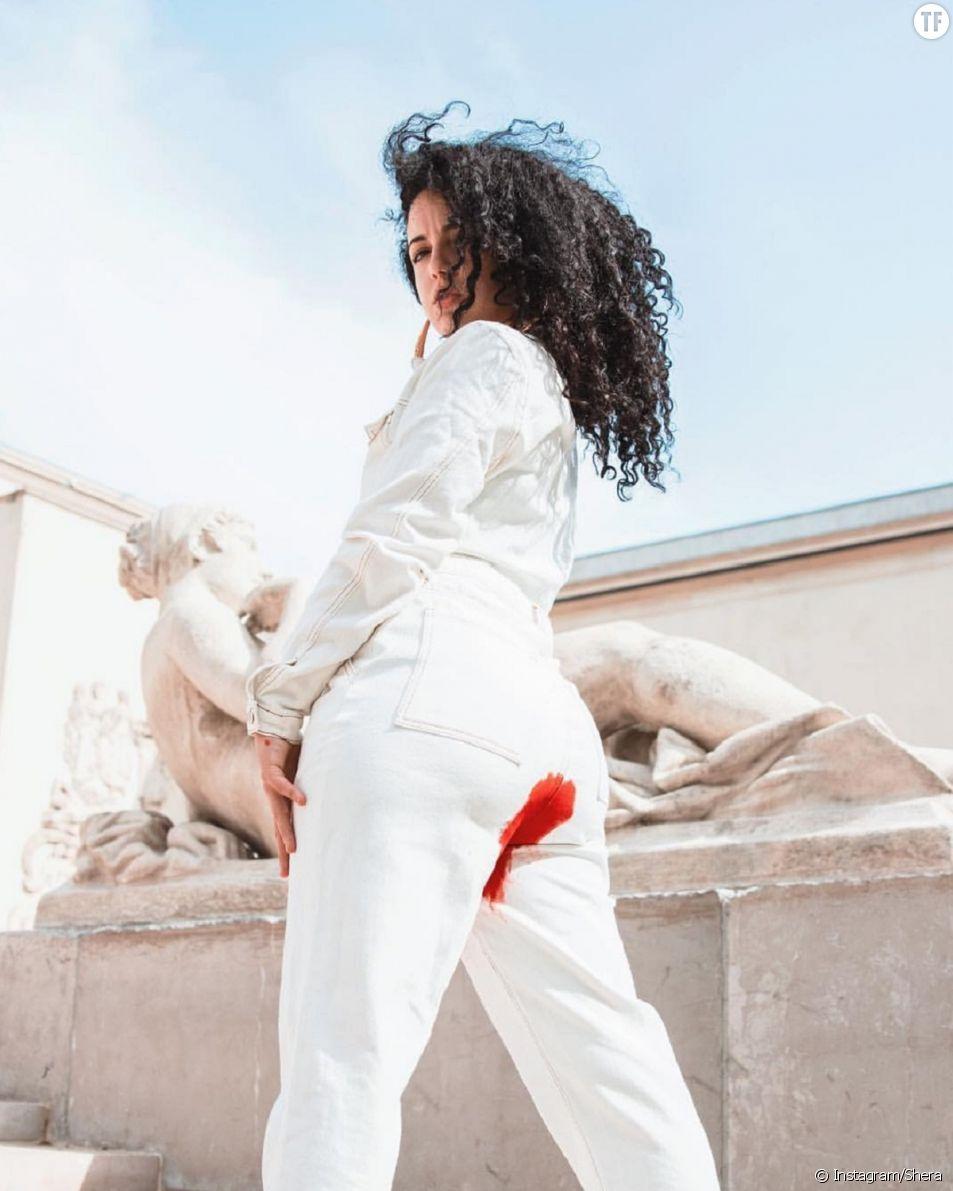 La Youtubeuse Shera pose avec une tache rouge sur son pantalon contre le tabou des règles
