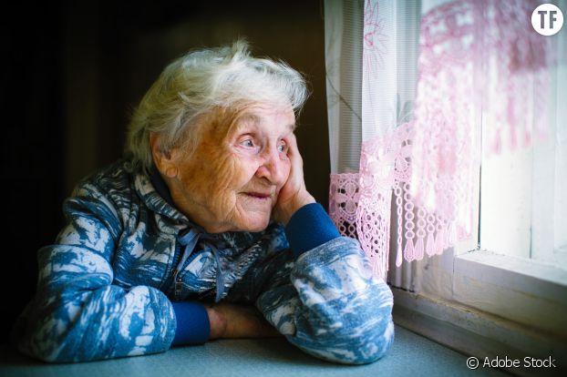 Personne âgée regardant par la fenêtre