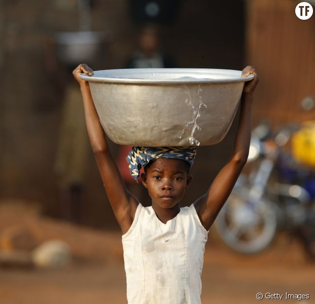 Le portage d'eau par une petite fille en Afrique