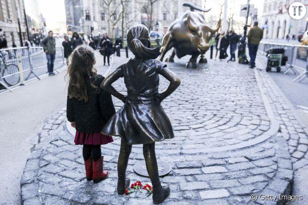 """Une fillette posant fièrement à côté de la statue """"Fearless Girl""""."""
