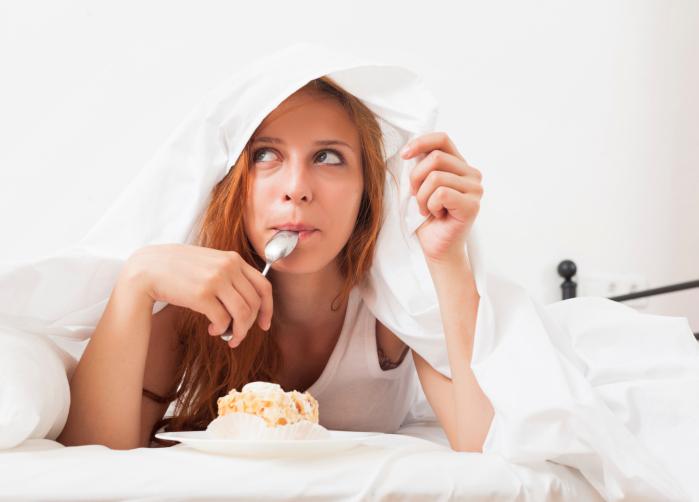 Jeune femme réflêchissant tout en mangeant un gâteau au lit